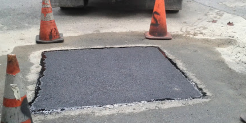 asphalt repair with orange cones surrounding it