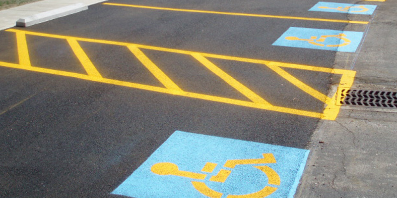 Multiple ada handicap parking lot marking - blue square with handicap symbol in it