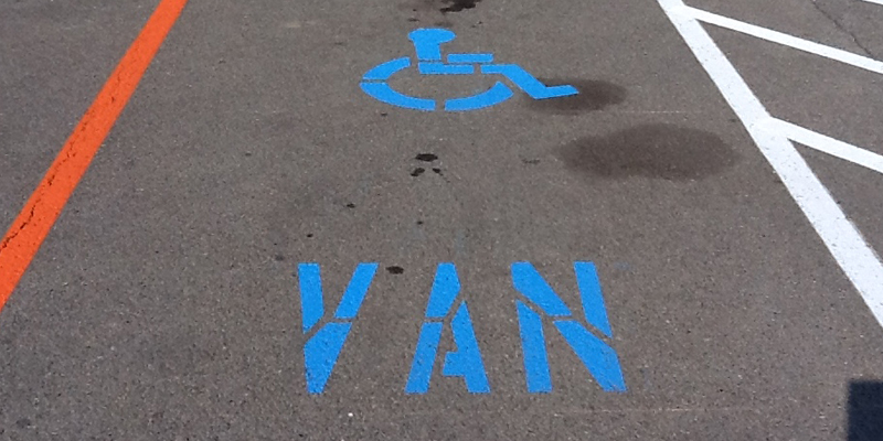 blue van and handicap markings in a parking lot - just one parking space