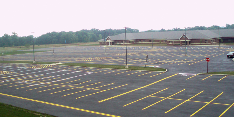 wide shot of the parking lot of a brand new school with yellow markings