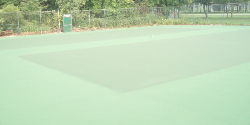 tennis court with no markings. Just a green floor with a fence around it