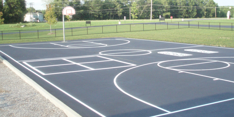 asphalt basketball court with new white lines including three point line, free throw lines and lane and out of bounds baseline and side lines.