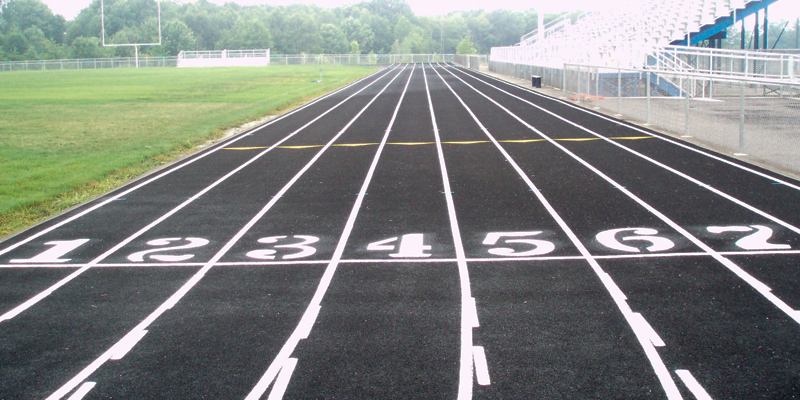 starting line of a school track that has 7 lanes all marked one through seven