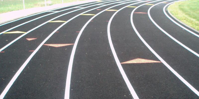 the bend of a school track that has starting triangles for the 200 meter or 400 meter race