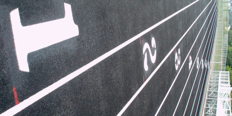 sideways shot of staggered numbers one through eight high school track lanes